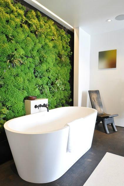 Una bañera blanca de estilo minimalista, enmarcada por un   jardín vertical.