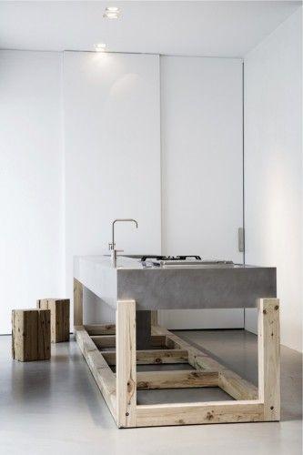 La original y robusta isla de una cocina, fabricada con cemento y madera.