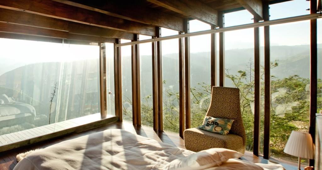 Una casa de madera, con un dormitorio donde predomina el cristal.