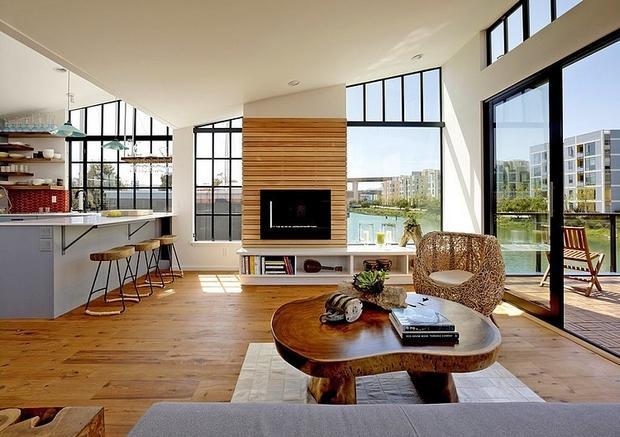 Un salón con  una chimenea situada entre dos ventanales.