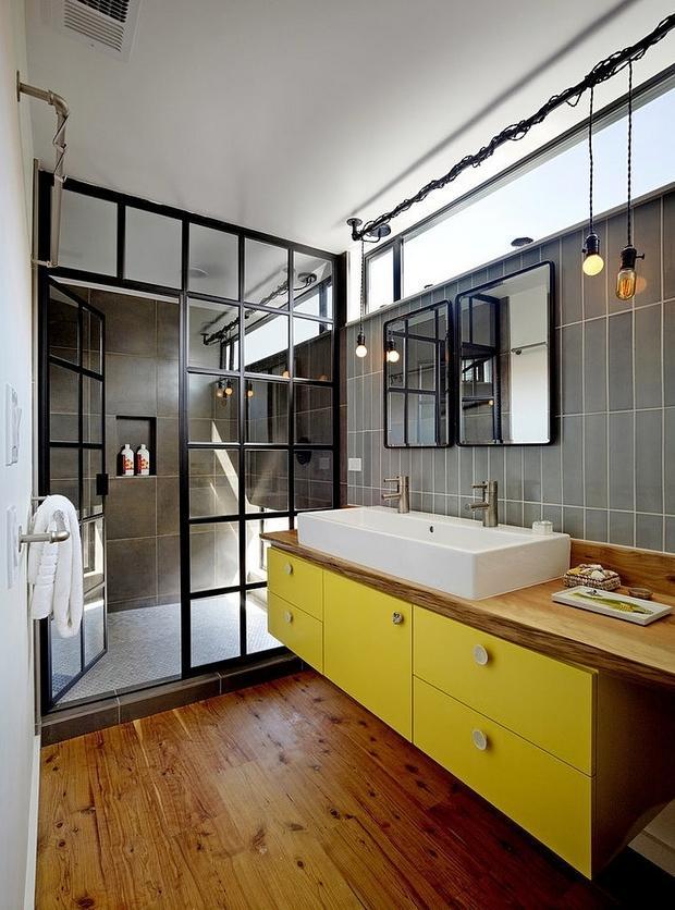 Un cuarto de baño gris, negro y blanco con un toque de amarillo.
