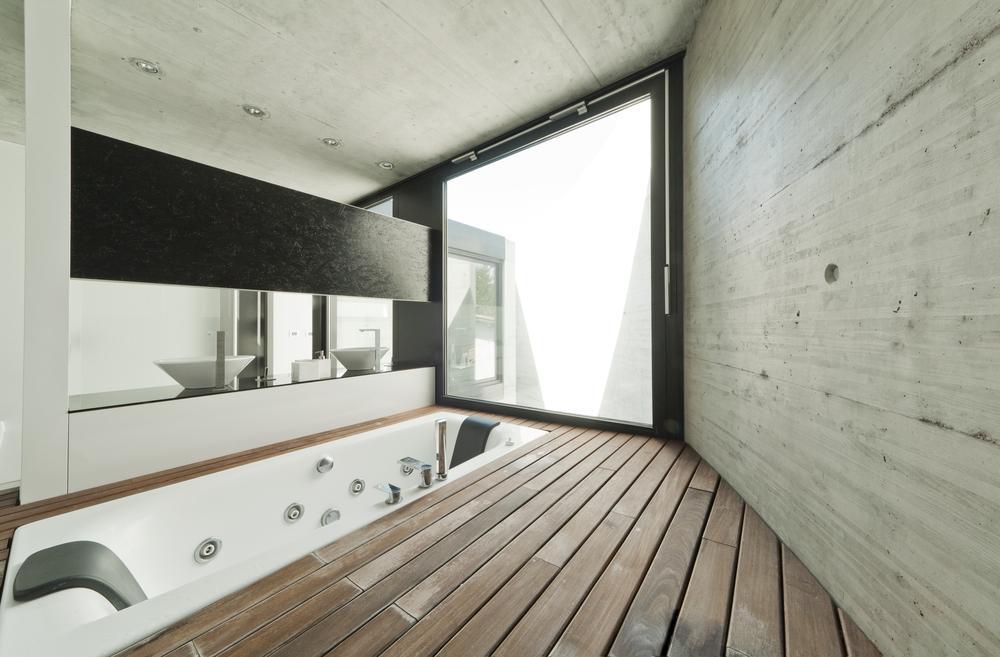 Un  cuarto de baño de hormigón, con un suelo de teka y una moderna bañera encastrada en el.