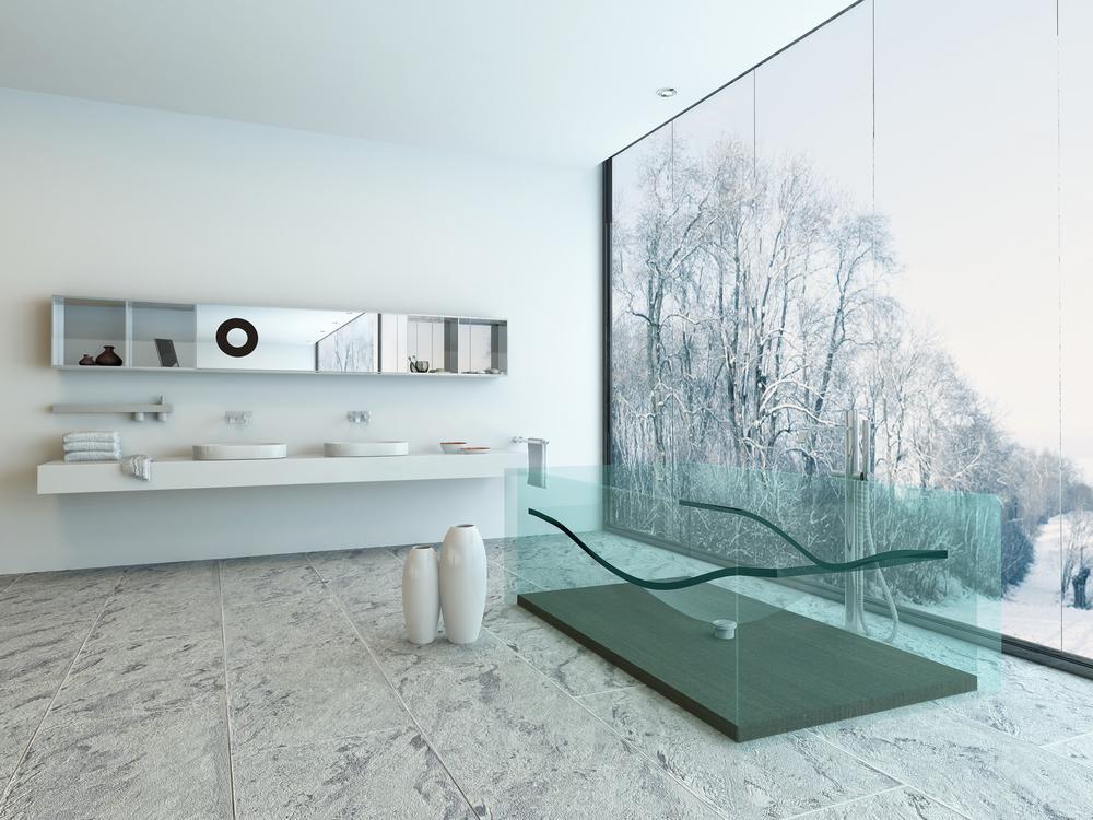 Una bañera transparente, en un cuarto de baño de estilo minimalista.
