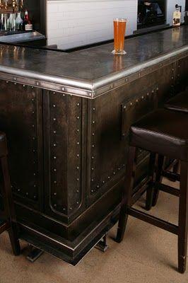 Una barra de bar, metálica con dos distintos acabados y  multitud de remaches.