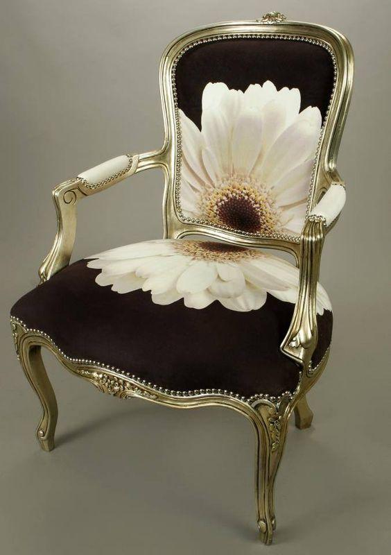 Un sillón de estilo barroco, con una margarita blanca, en su tapicería de fondo negro.
