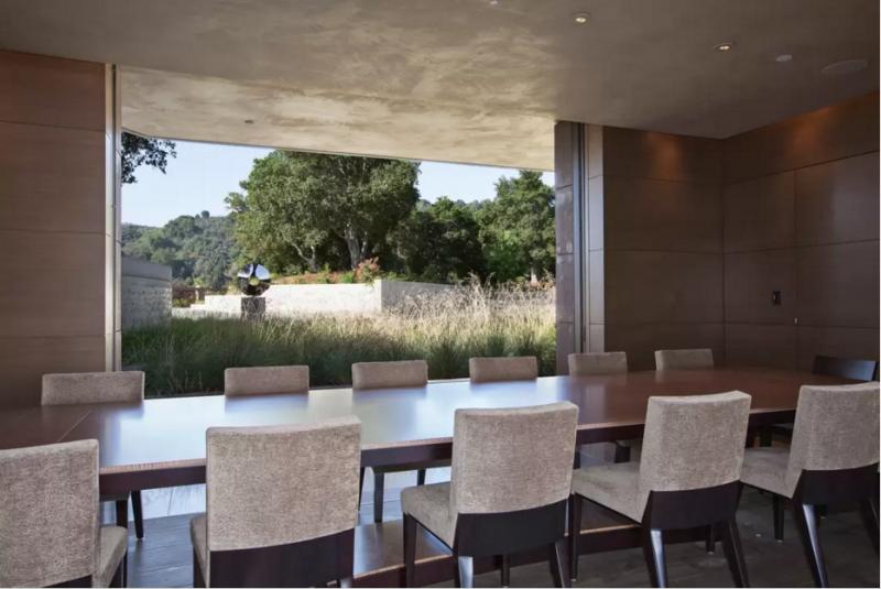 Un comedor minimalista, con una enorme mesa para catorce comensales.