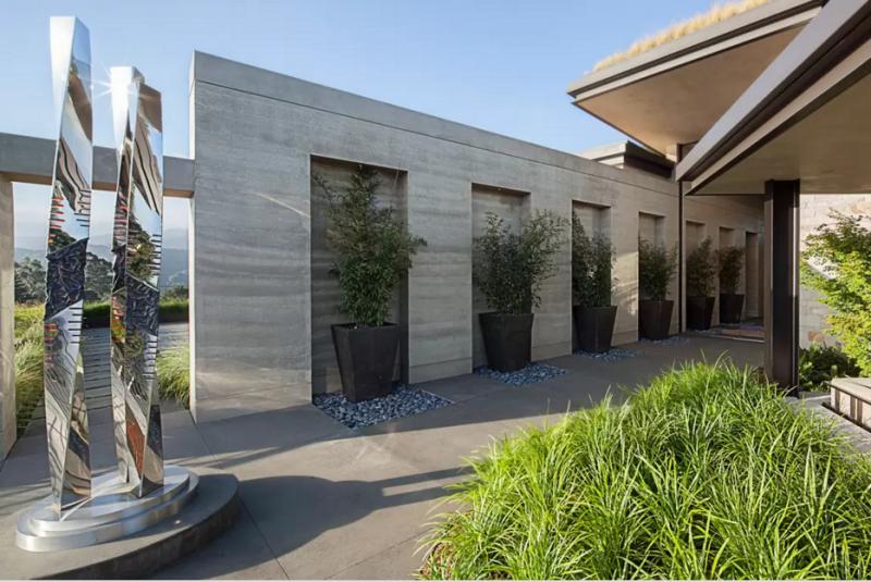 Imagen de la entrada exterior con una alta y brillante escultura.