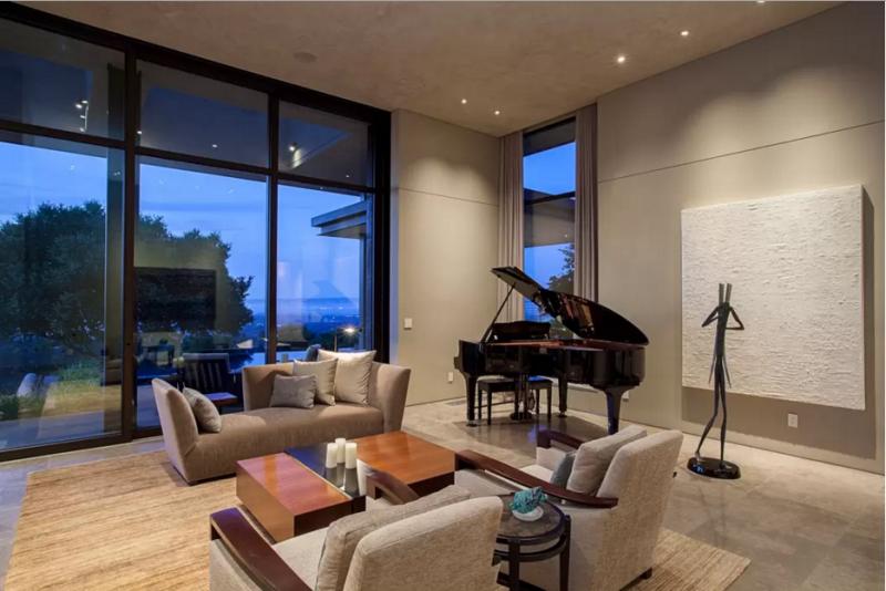 Zona de música al otro lado de la chimenea, con un piano de cola.