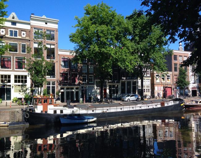 En la imagen una barcaza, en un canal de la ciudad de Amsterdam.