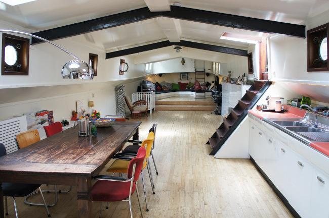 Un interior en tonos claros, con una mesa de comedor rústica y sillas apilables en primer termino.