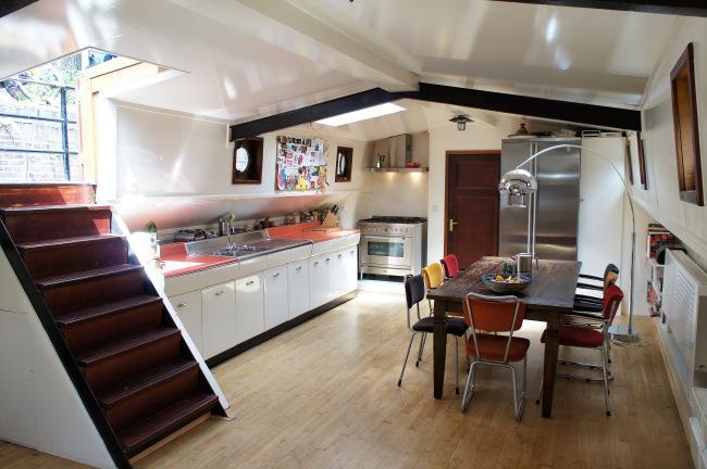 La cocina combina el blanco del mobiliario, con el tono rosado de la encimera.