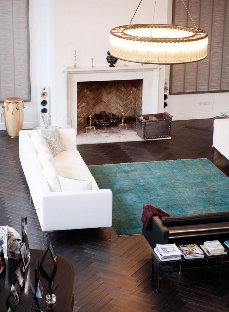 Contraste entre el suelo de madera oscura, con los sofás y la chimenea blanca.