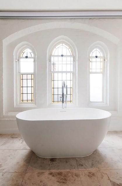 Un luminoso y moderno cuarto de baño, con una bañera junto a las vidrieras.