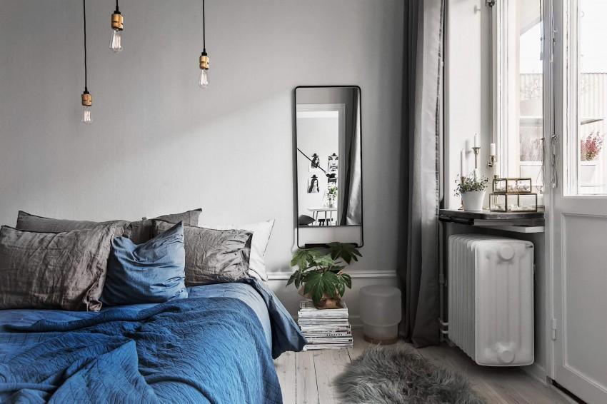 Un dormitorio con una interesante combinación de tonos, blancos, grises y azul.