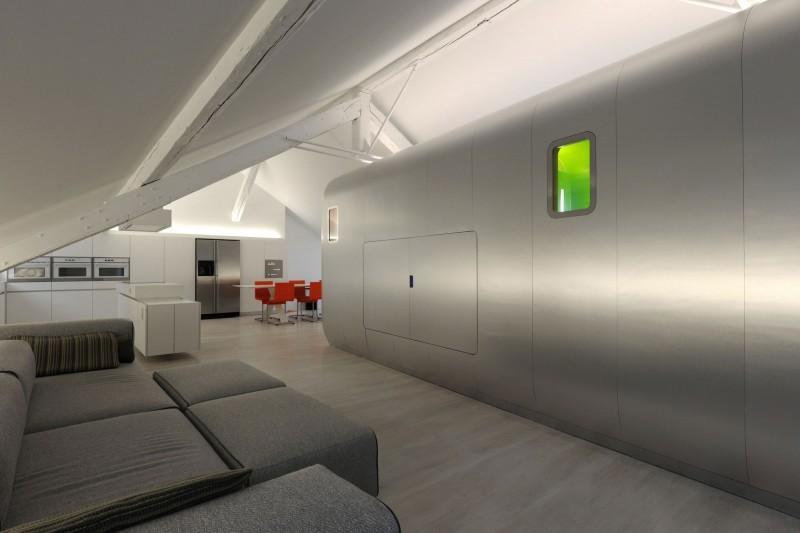 La zona de salón, con suelo de tarima en tonos grisáceos, a juego con el sofá y el frontal de aluminio.