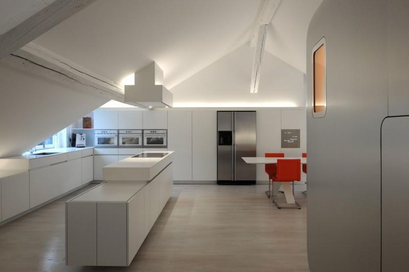Una imagen de la cocina y del comedor, con una mesa rodeada de sillas naranja.