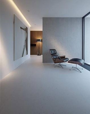 Junto a una pared de hormigón y el ventanal un relajante sillón de lectura.