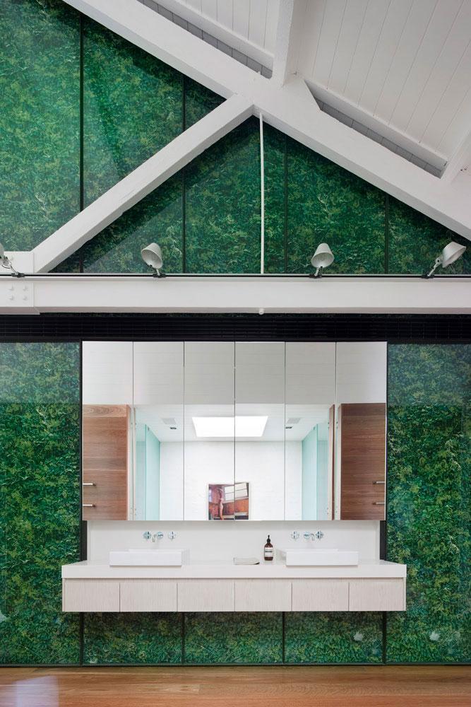 Un cuarto de baño con unos enormes ventanales, con un fondo vegetal.