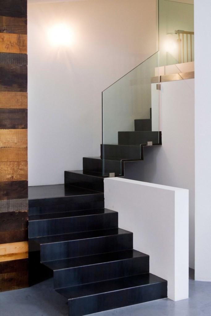 Mezcla de materiales como la madera de la pared y el acero de los peldaños de la escalera.