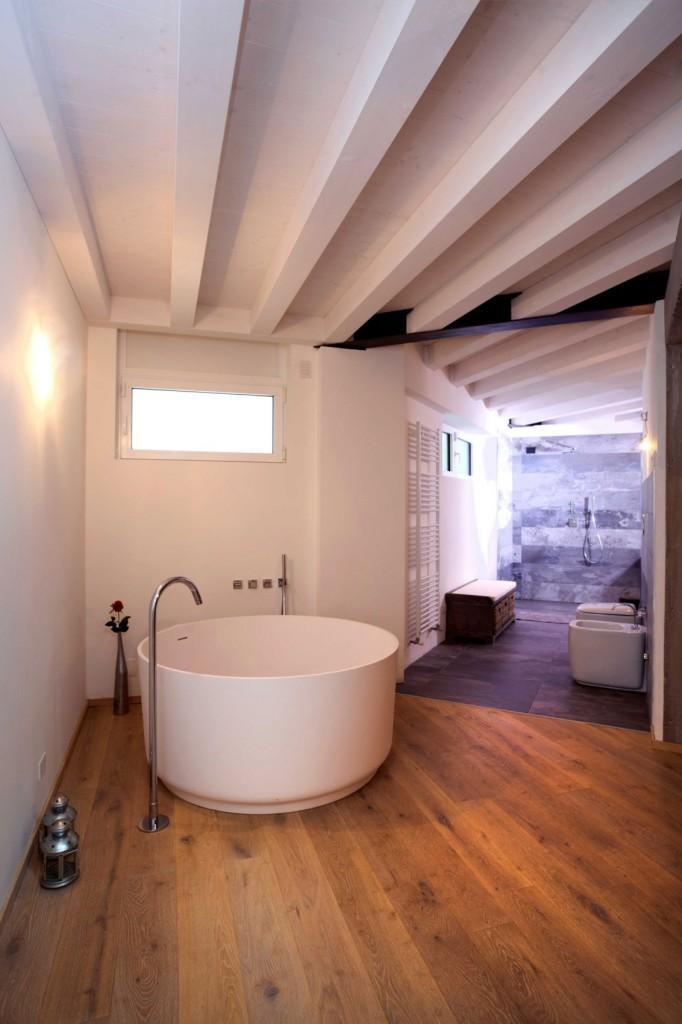 Madera, piedra y sanitarios de diseño en la decoración del amplio cuarto de baño.