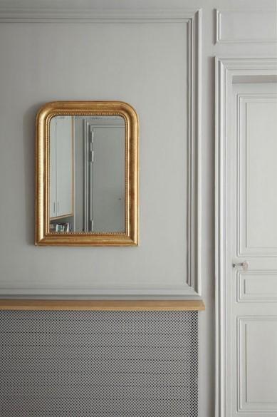 Un radiador reconvertido en consola, con un espejo sobre ella.