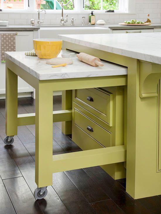 Una mesa se desliza bajo la original isla, de esta moderna cocina.