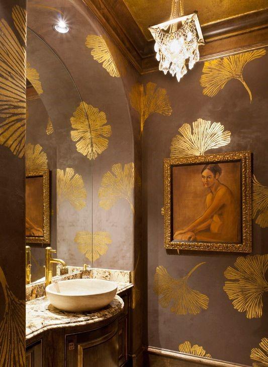 Unas grandes hojas doradas, sobre fondo marrón, decoran este elegante cuarto de baño.