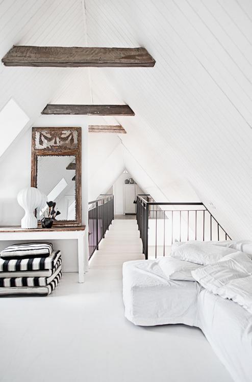 Un techo abuhardillado con guesa y viejas vigas de madera.