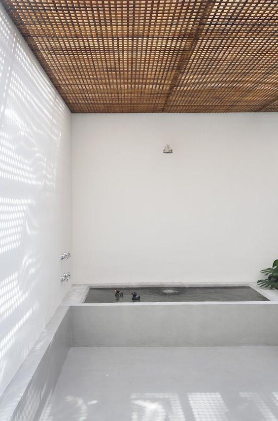 Una celosía con pequeños cuadrados de teca, sobre una zona de baño en el exterior.