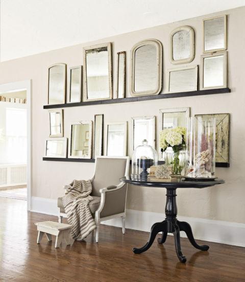 Un par de estrechas baldas de color oscuro sirven en este caso para apoyar espejos.