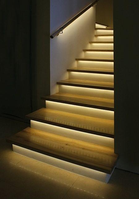 Una linea de luz escondida en la parte inferior de los peldaños de madera.