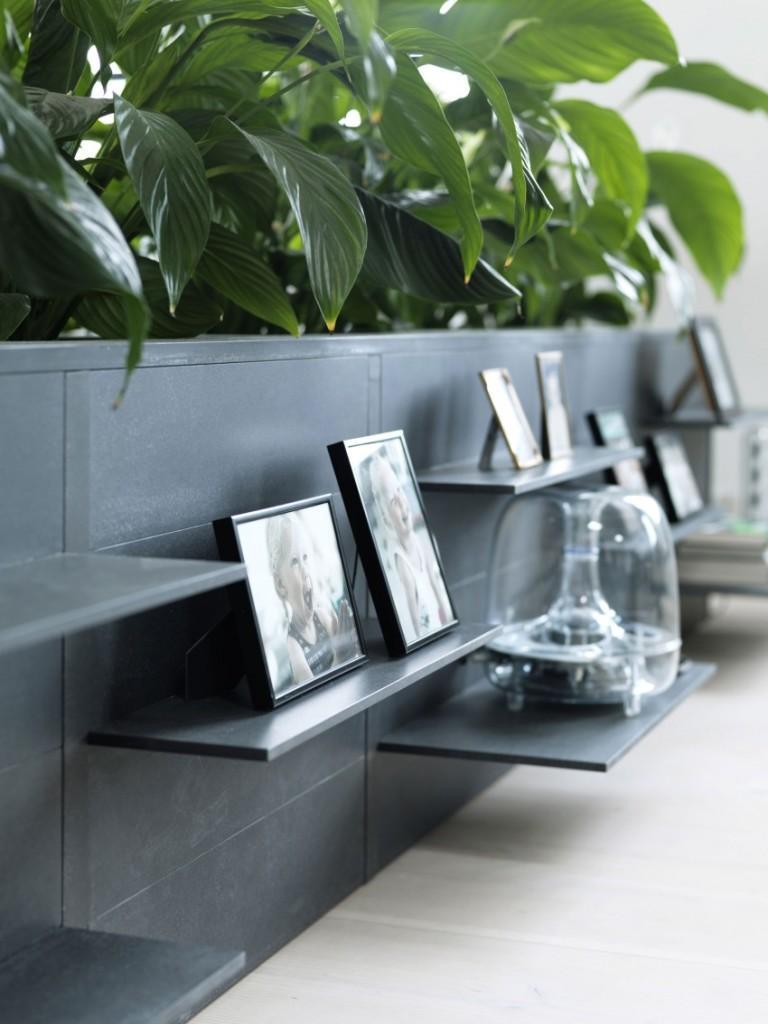 Una original forma de tener plantas en el salón, es esta que aúna jardinera y mueble con baldas.