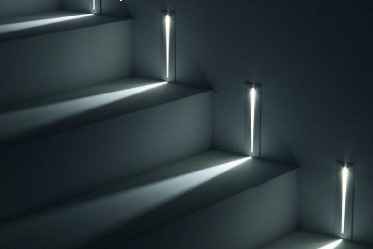 Piezas encastradas en la pared iluminan cada uno de los escalones.