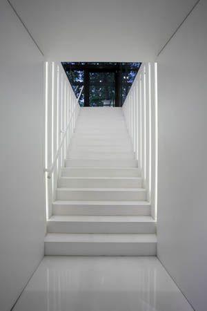 Largas y estrechas bandas verticales de luz, señalizan cada peldaño de esta escalera.