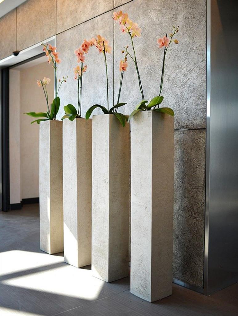 Algunos floreros altos que parecen columnas marcan una entrada imponente en un edificio.