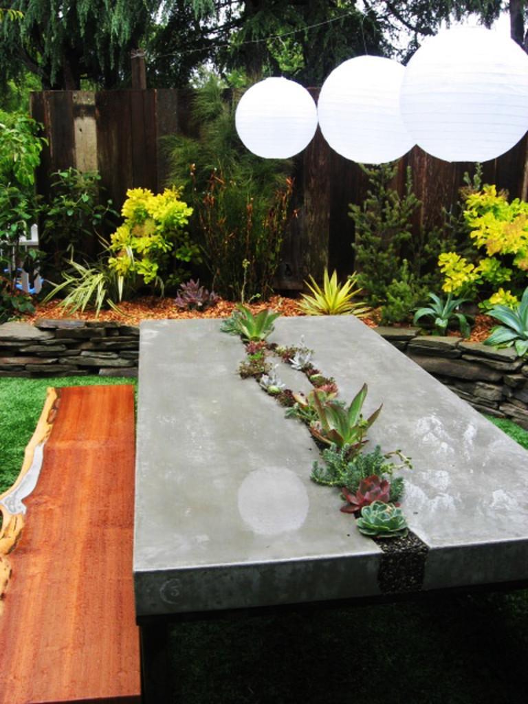 En el jardín, una mesa de comedor con el centro de mesa incorporado.