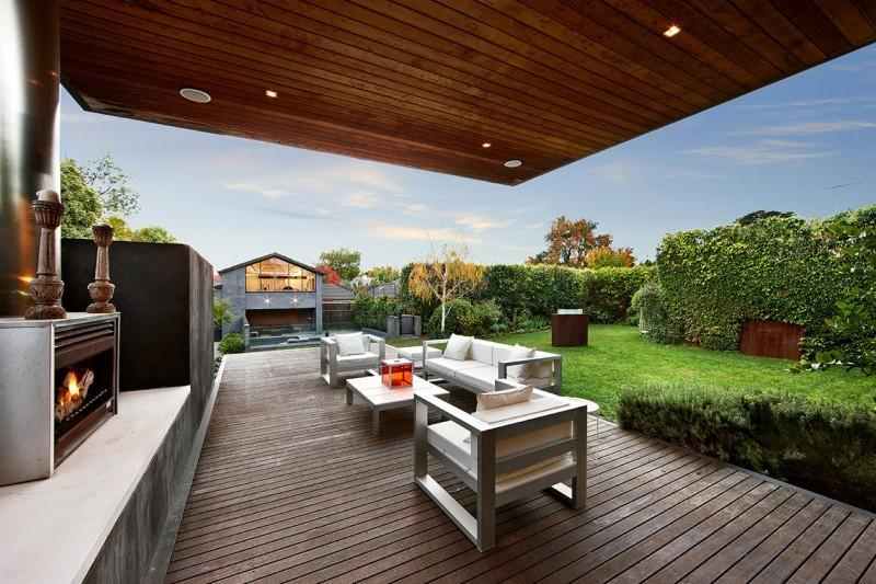 Suelo y techo cubierto con finas lamas de madera, en la zona de sofás del jardín.