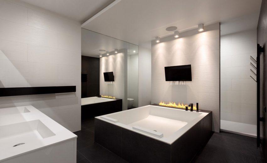 Junto a un gran espejo de suelo a techo, vemos una bañera de hidromasaje.
