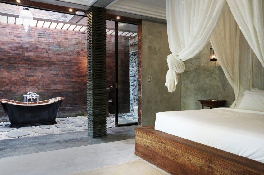 Una bañera clásica en tonos cobrizos, en el baño al aire libre.