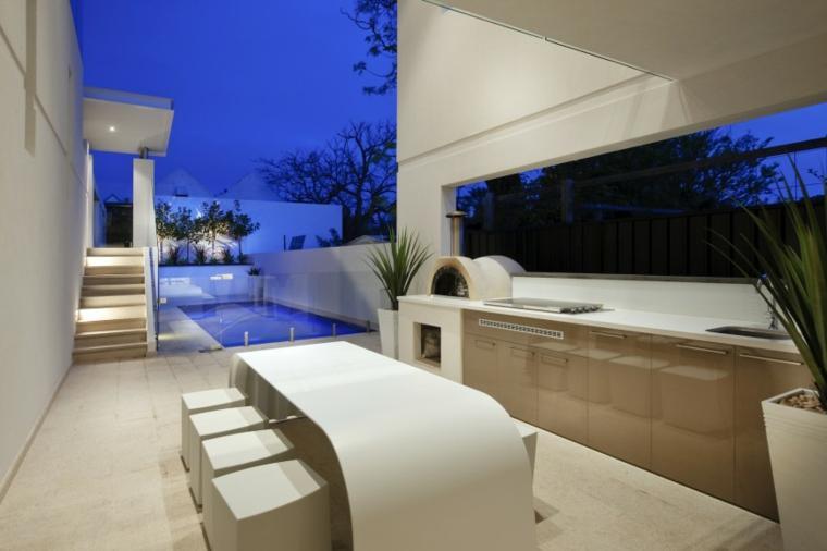 En esta moderna cocina de exterior, una mesa con formas redondeadas.