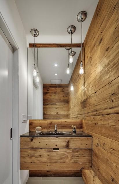 Un aseo revestido de madera en tres de sus paredes, con un acabado muy actual.