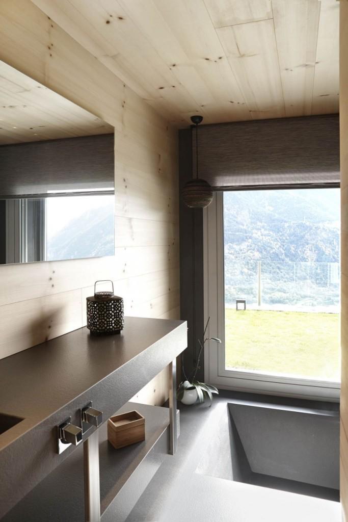 Una bañera junto al ventanal, del mismo material que el suelo.