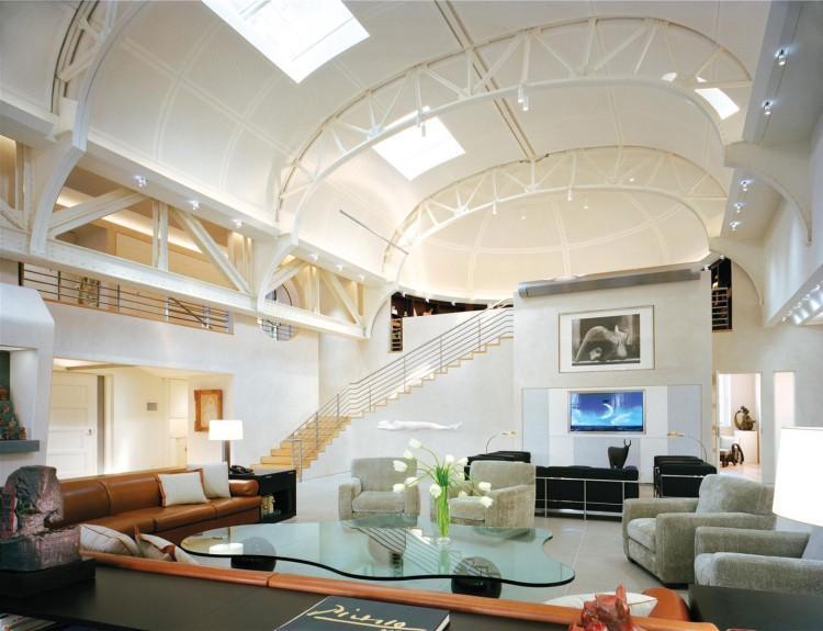 Una curva biblioteca, acoge el sofá de piel marrón de este gran salón.