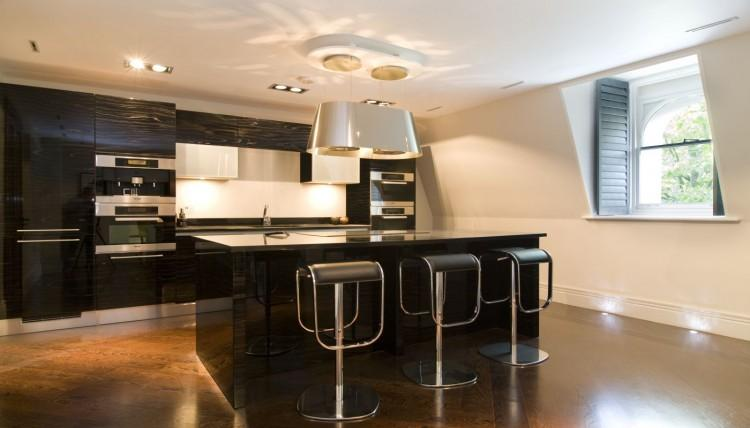 En la cocina de este ático, se optó por el color negro con acabado muy brillante.