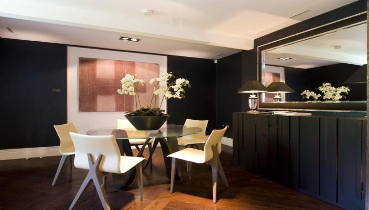 Otro comedor con un original aparador negro, con espejo enmarcado también en negro.