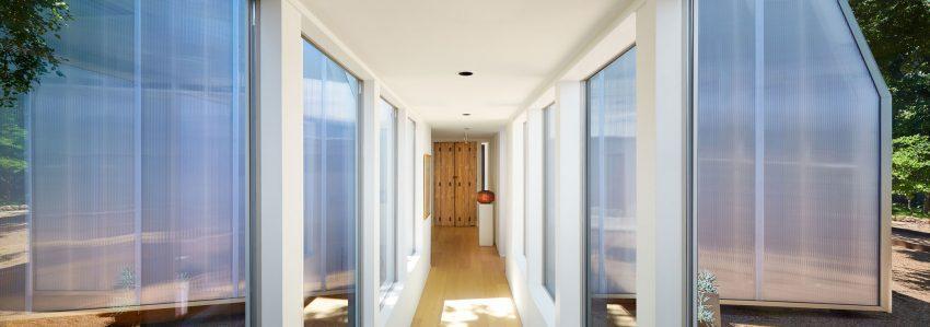 Al fondo del largo pasillo, contrasta una antigua puerta de madera de estilo rústico.
