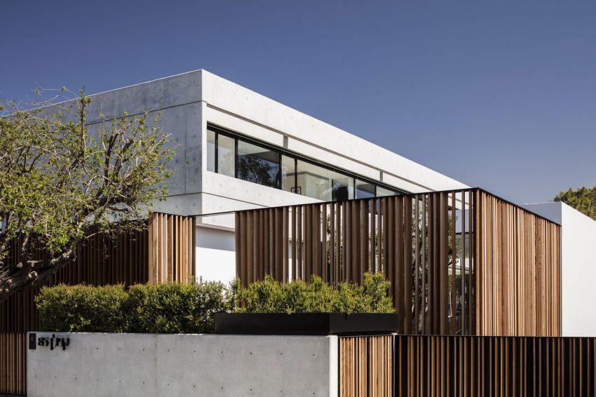 En un suave tono gris del hormigón, blanco , negro y tonos madera se muestra esta moderna vivienda.