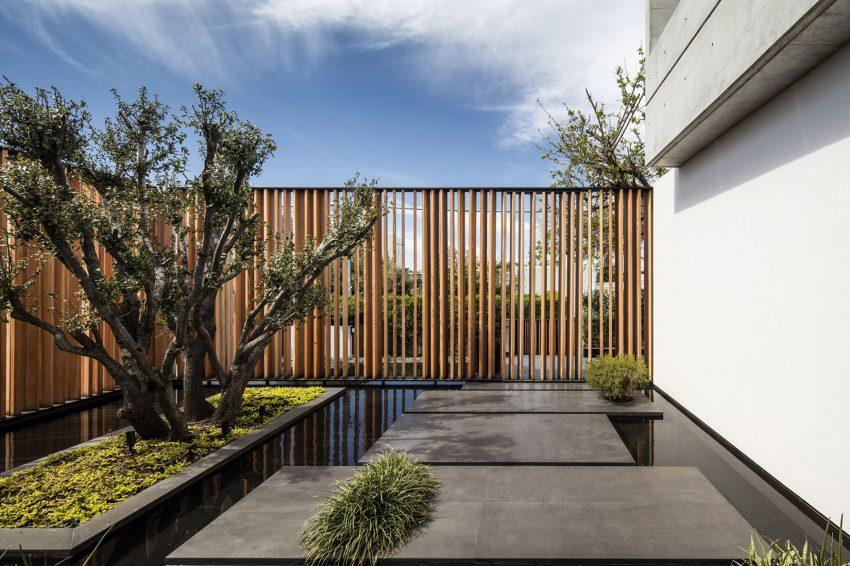 Un jardín zen, con bloques de hormigón que albergan la vegetación.