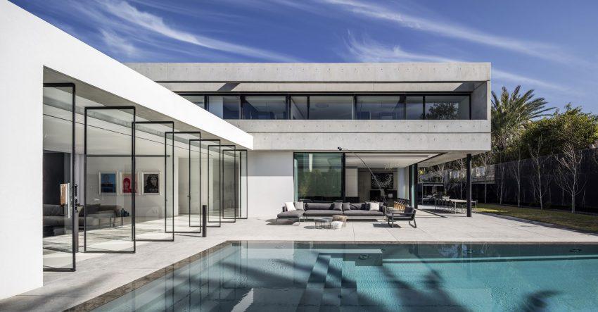 Imagen de la fachada exterior con las grandes cristaleras pivotantes, que dan acceso a la zona de la piscina.
