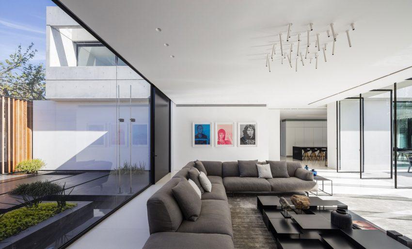Sobre la zona de sofás unas originales y minimalistas lámparas que son tubos con puntos de luz LED.